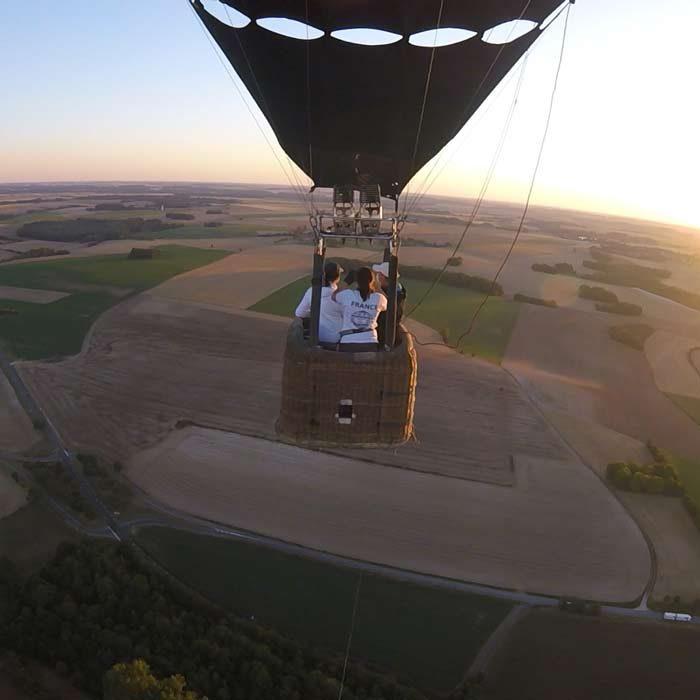 Montgolfière dans le ciel avec vue sur les champs et les personnes à bord Airshow à Haudivilliers Loisirs